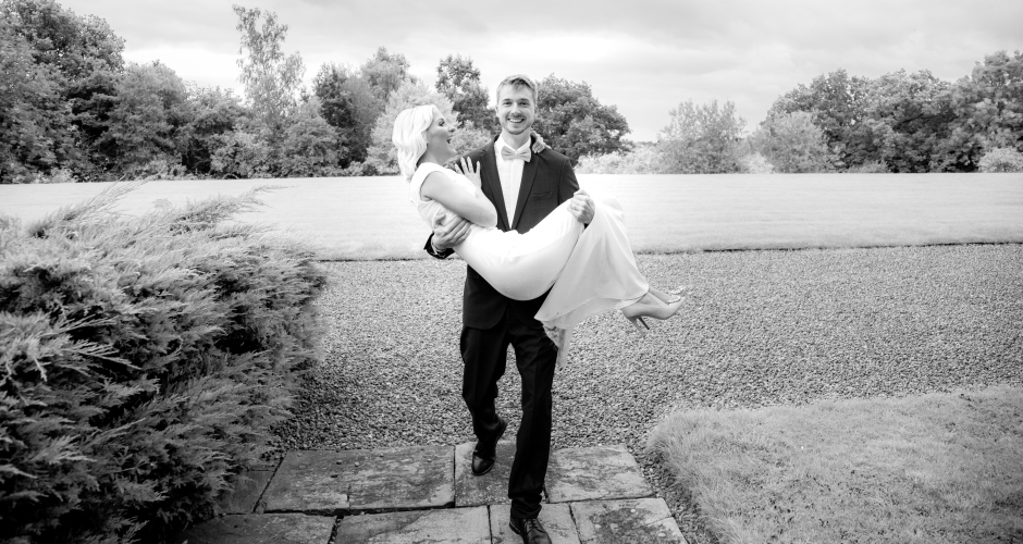 The groom carries his bride at Crathorne Hall