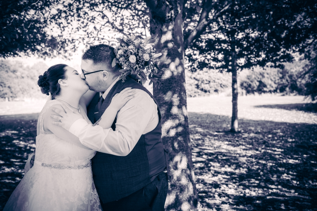Wedding couple kiss under the trees at the Sporting Lodge.