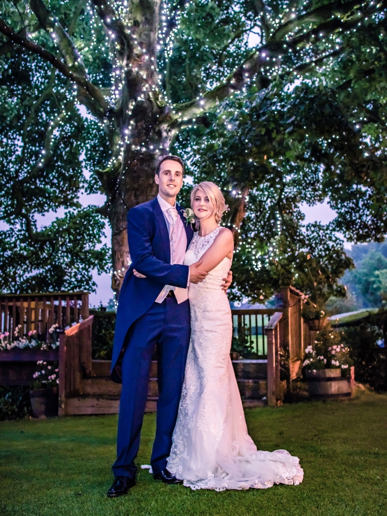 Wedding couple pose for a photograph under a lit up tree.